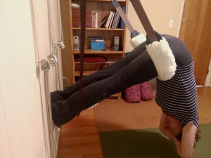 photo of down dog yoga pose variation, hanging from yoga swing.