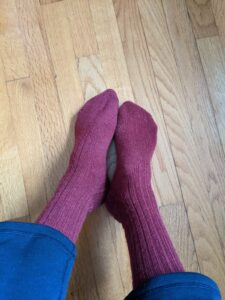 A photo of wool socks that have been dyed a purple-red
